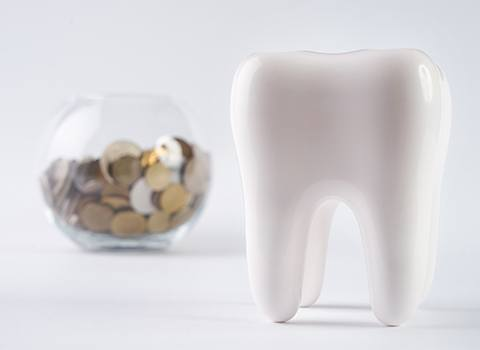 A tooth sitting next to a bowl of coins