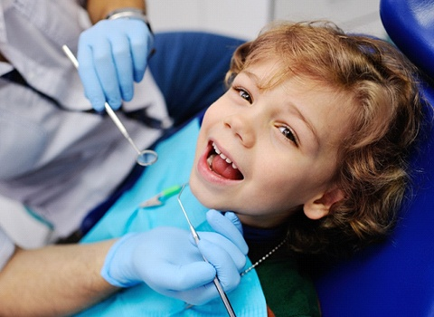 A little boy having his teeth checked at the dentist office